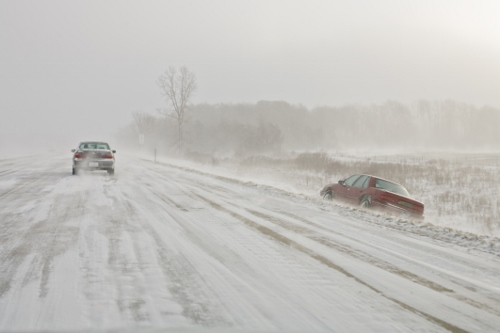 Car in ditch on snow covered highway