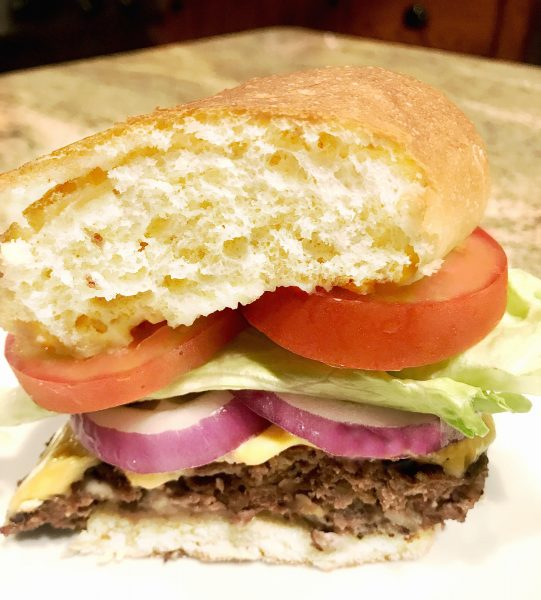 Hamburger patty topped with onion, lettuce and tomato.