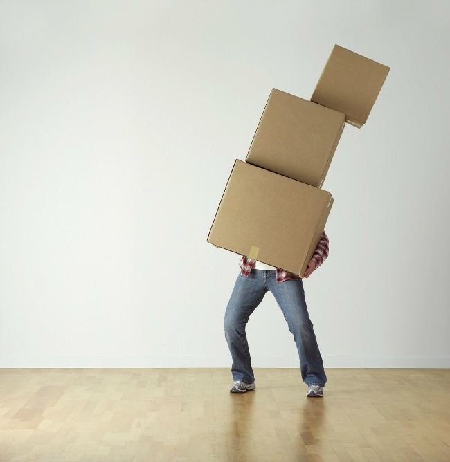 Man holding stack of falling moving boxes