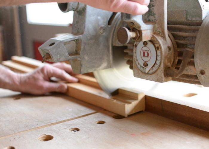 carpenter using a saw to trim a molding