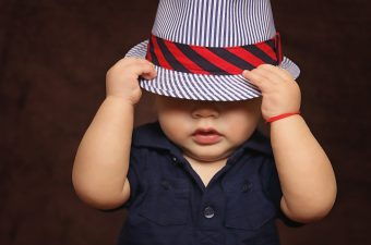 child with hat pulled over eyes