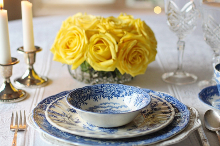 blue and white dishware with yellow flower centerpiece