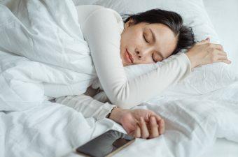 woman sleeping on bed near smartphone
