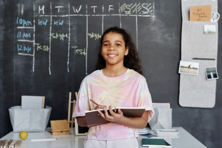 girl in front of chalkboard smiling