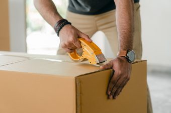 person taping up a moving box
