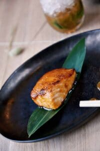 crispy salmon on a black plate