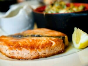 dinner plate with salmon and a lemon wedge in focus