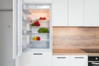 open refrigerator with a variety of vegetables stored
