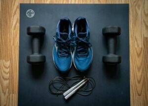 blue and black athletic shoes surrounded by dumbbells