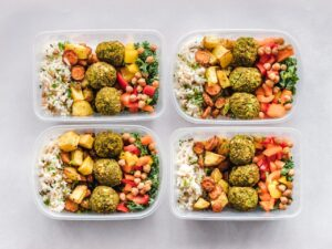 4 identical dishes of food in to-go like containers (meal prepping)